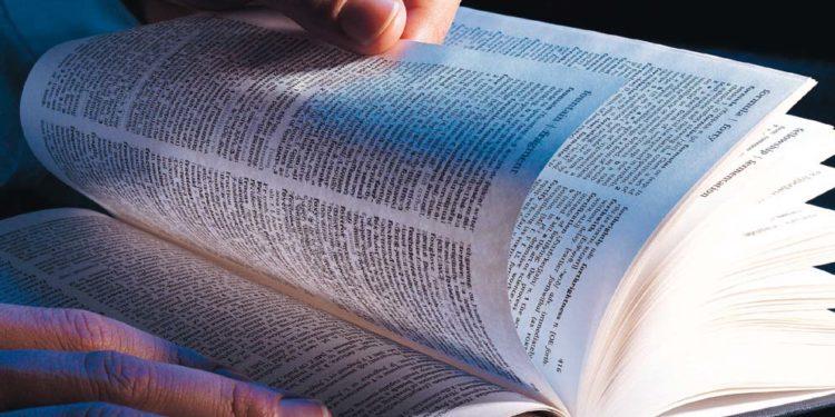 072022B - Hands flicking through text book.